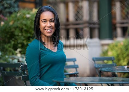Beautiful young african-american girl sitting at street cafe and smiling looking at camera