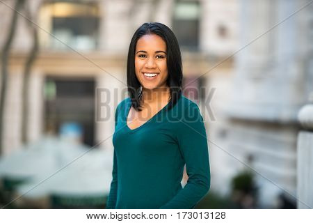 Beautiful hispanic african-american young adult woman smiling outdoors and looking in camera