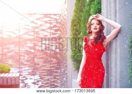Snow Queen in red. Winter woman in crown in a red dress and red lipstick. Girl with snowflakes, rear view, Back