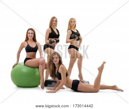 Pretty sportswomen in black tops and shorts posing in studio one of them sitting on a green fitball