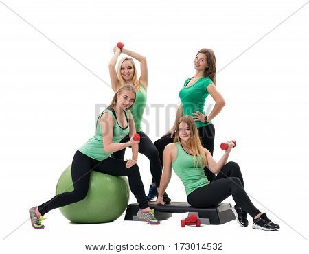 Pretty sportswomen in green tops and black leggings posing in studio with red dumbbells in their hands one of them sitting on a fitball