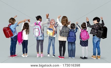 Rear view group of diverse kids standing in a row holdings hands in the air