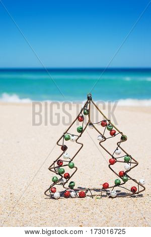 Small metal Christmas tree with jingle bells on the beach. New Year and Christmas holiday concept