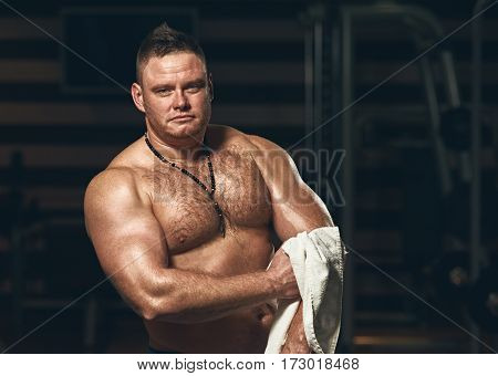 Portrait of muscular man wiping sweat after hard training