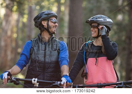 Biker couple smiling and looking at each other in countryside