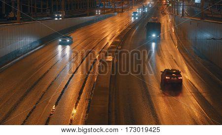 Cars going on night city street in golden light