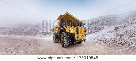 Big yellow mining truck at an open pit