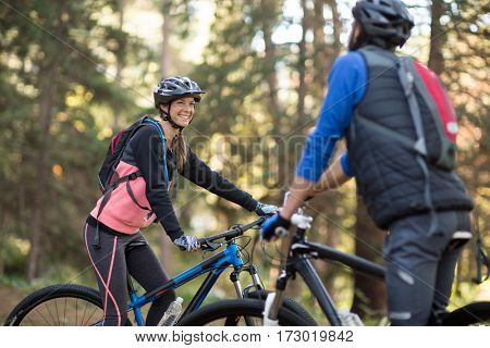 Biker couple smiling and interacting with each other in countryside
