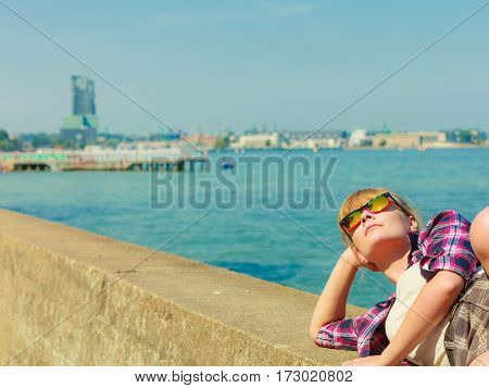 Summer vacation relax and traveling concept. Young tourist woman hiker relaxing on sea shore enjoying sunlight
