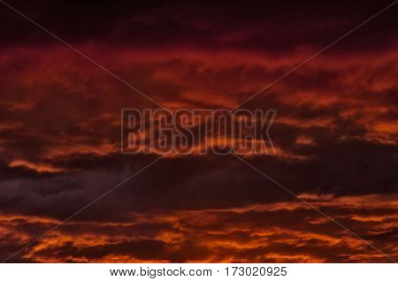 the storm sky with various shades of red color with dark clouds