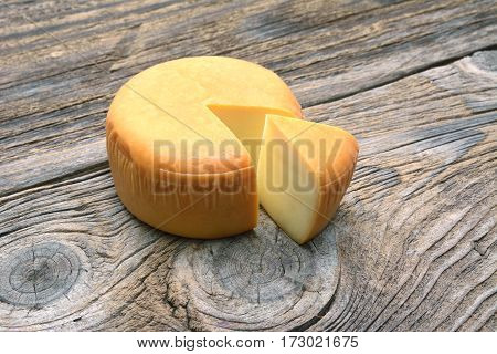 Cheese wheel isolated on old wooden table