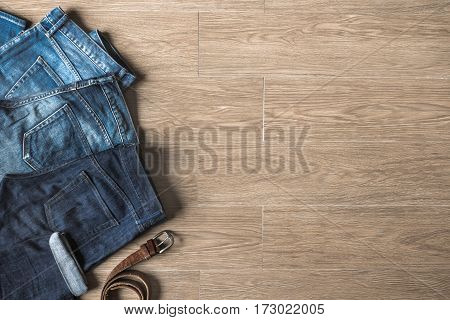 Top View Of New Jeans And Faded Jeans With Copy Space On Wood Background