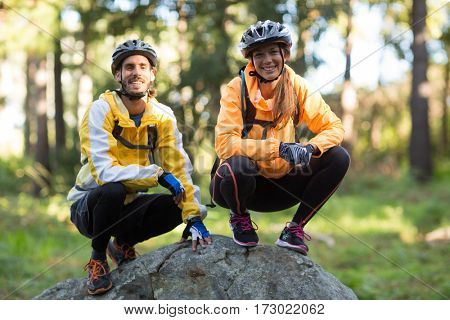 Portrait of biker couple smiling in countryside forest