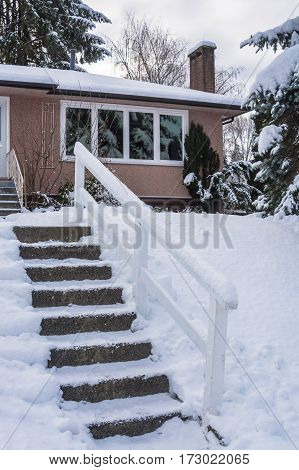 Stair way to the entrance of family house over front yard in snow. Residential house on winter cloudy day