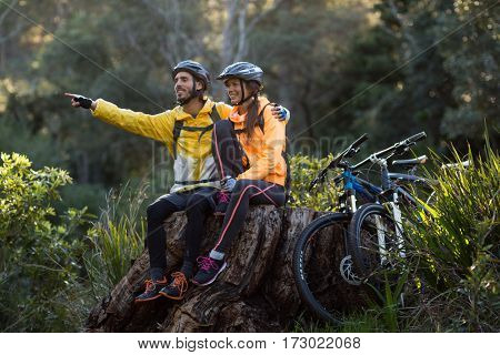 Biker couple sitting and pointing in distance at countryside forest