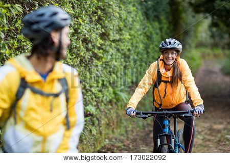 Biker couple interacting while cycling in countryside forest
