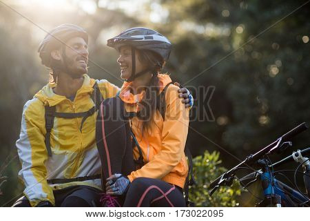 Biker couple sitting and interacting with each other in countryside forest