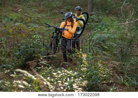 Biker couple carrying their mountain bike and walking in countryside forest