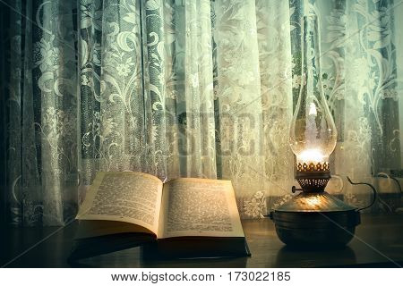 old book on the table, a kerosene lamp and glass of wine