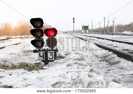 Traffic light shows red signal on railway. Prohibiting signal. Railway station.