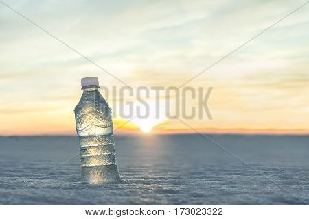 Bottle of cold water in the snow at sunset. Advertising by mineral water. Quenching thirst. Fresh frosty morning. Close-up view on the background of beautiful nature.