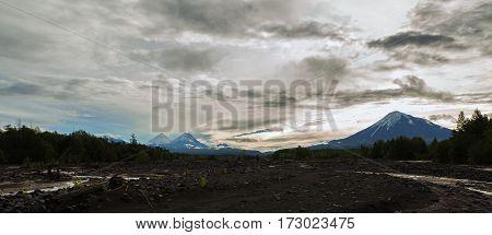 View of the volcanoes: Ostry Tolbachik, Klyuchevskaya Sopka, Bezymianny, Kamen from river Studenaya at dawn. Kamchatka Peninsula.