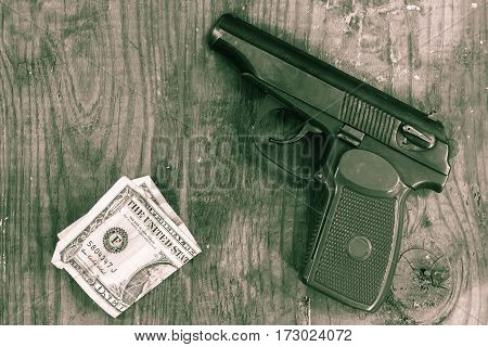 The gun and money on wooden table. Concepts: crime contract killing killer robbery extortion money laundering.