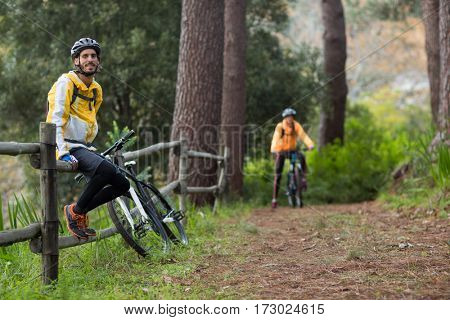 Male biker sitting on fence in countryside forest