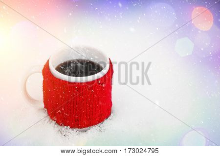 Cup of hot coffee on the snow. Feeling of comfort and holiday mood. Xmas and New Year fairy tale background with sparkling bokeh lights. Beautiful greeting card. Picturesque bright composition.