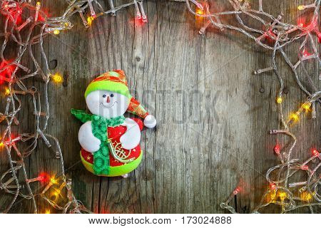 Colorful Christmas garland lights and smiling snowman on wooden rustic background. Christmas decorations. Holiday mood. Beautiful New Year composition.