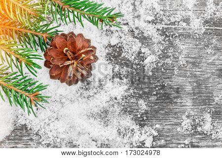 Christmas tree and cones on the old wooden table. Picturesque winter composition. Holiday mood. Xmas and New Year fairy tale background. Beautiful greeting card.