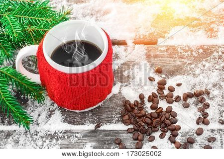 Cup of hot coffee on the old snowy table and christmas tree branch in sunshine coffee beans. Feeling of comfort and holiday mood. Xmas and New Year fairy tale background. Beautiful greeting card.