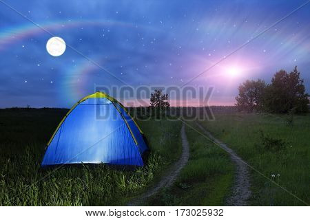 Alien spaceship - UFO over the field at night. Camping tent glows under a night sky full of stars. Outdoor Camping adventure. Travel concept. Extraterrestrial life. Invaders from another planet.