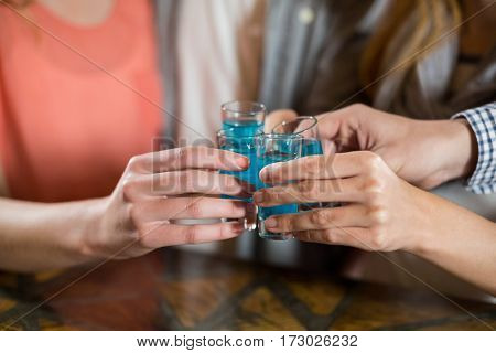 Mid section of friends having tequila shots in bar