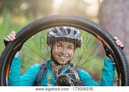 Portrait of female biker repairing mountain bike in countryside