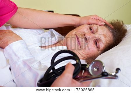 Picture of a sick elderly woman with her carer holding a stethoscope