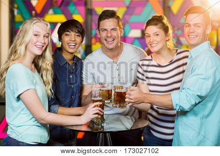 Portrait of smiling friends having glass of beer in party at bar