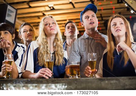 Upset fan watching football at bar counter in bar