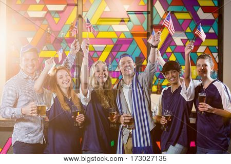 Group of smiling friends holding american flag in party at bar