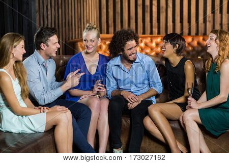 Smiling friends interacting with each other at bar