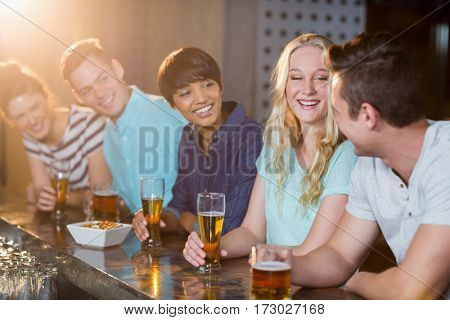 Group of smiling friends interacting with each other while having beer at bar counter in bar