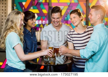 Group of smiling friends toasting glass of beer in party at bar