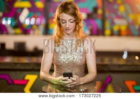 Young woman using mobile phone in bar