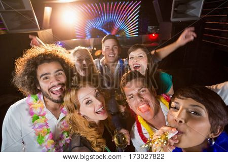 Portrait of smiling friends having fun in bar