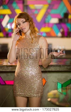 Young woman talking on mobile phone at bar counter