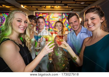 Portrait of smiling friends toasting glass of cocktail in bar
