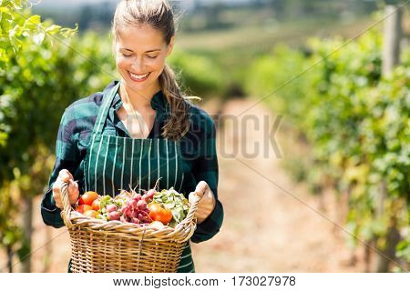 Happy female farmer holding a basket of vegetables in the vineyard