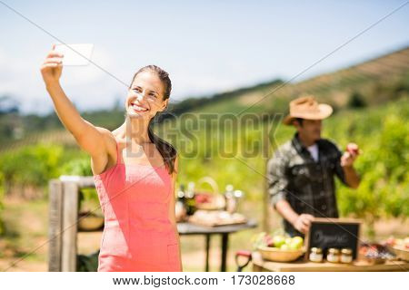 Female customer taking a selfie in front of vegetable stall at local market