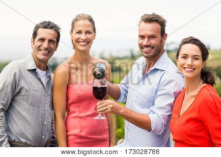 Portrait of happy friends having wine in the vineyard