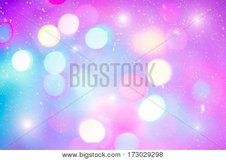 Defocused colorful ligths of Christmas tree. Multicolored bokeh lights during a snowfall. Background for greeting card. Winter composition. Happy holiday mood. Xmas and New Year fairy tale wallpaper.